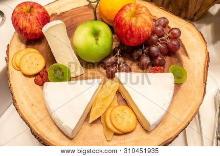 brie cheese with variety of fruit and cracker on wooden plate in buffet line