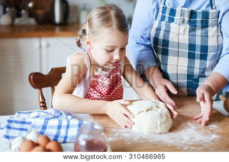 Kid Is Making Dough. Family Is Cooking In Kitchen. Child Is Baking Homemade Pastries Or Pizza. Child