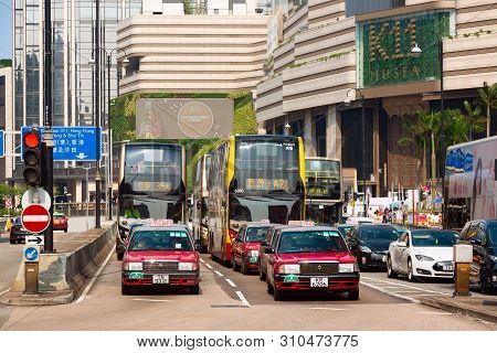 Hong Kong, Sar China - May, 2019 - Typical Hong Kong Taxi Cars And Buses On Nathan Road. Red Toyota