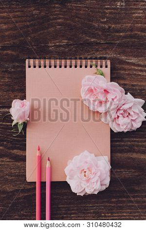 Blank Notebook With Pink Flowers And Pencils On Vintage Wooden Table. Flat Lay, Copy Space.