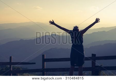 Woman on vacation relaxing in mountain. Summer vacation. Young woman traveler in vacation in nature. Traveler in vacation with backpack in nature. Girl traveler with hands outstretched in vacation. Traveler. Vacation . Backpack. Woman. Nature. Healthy lif