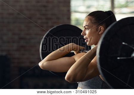 Fitness woman doing shoulder press exercise with a weight bar at gym. Muscular woman in gym doing heavy weight exercises. Concentrated athlete doing barbell lifting at health club with copy space.