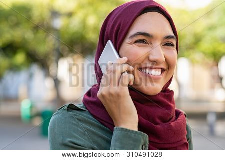 Young woman wearing hijab talking on cellphone in city park. Beautiful muslim girl talking on a mobile phone. Closeup face of islamic woman using a smartphone.