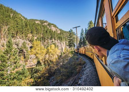 Young Man With A Cap Looks Out Of Train Window On The Historic Steam Engine Train Travelling From Du