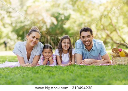 family, leisure and people concept - happy mother, father and two daughters laying on picnic blanket in summer park