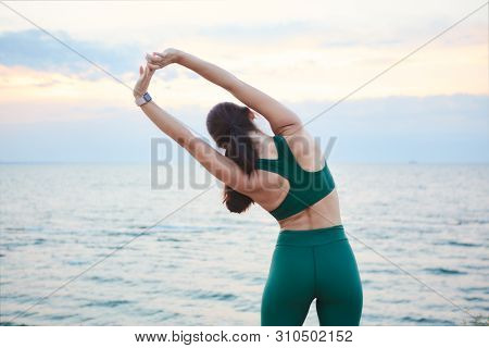 Young Brunette Woman Exercising At The Sea Shore At Sunrise Listening To The Music.