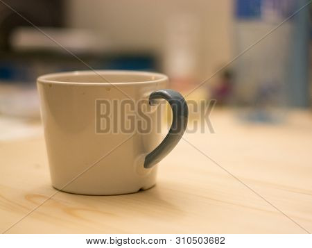 White And Blue Unwashed Cup Of Coffee On A Flat Wooden Surface In Front Of Bokeh Office Desk Backgro