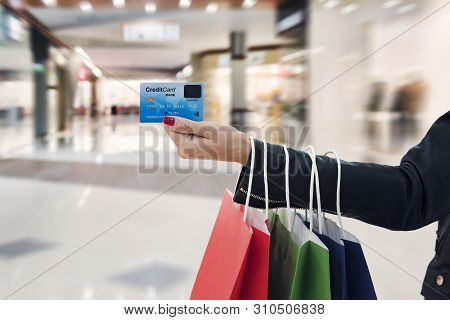 Crop Of Female Arm With Hanging Paper Bags Holding Credit Card At Blur Shopping Centre Background. C