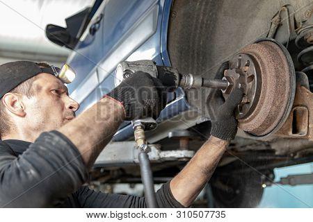 Car Mechanic Repairs The Rear Brake Drum, Unscrews With A Pneumatic Gun