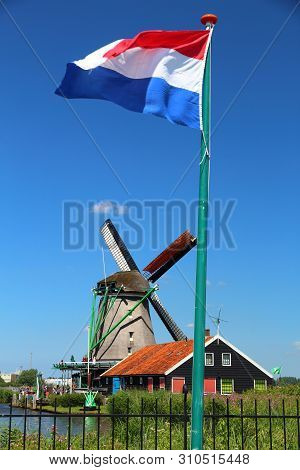 Windmill And Dutch Flag In Netherlands. Old Industrial Architecture In Zaanse Schans Rural Area In Z