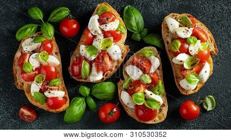 Bruschetta With Tomatoes, Mozzarella Cheese And Basil On A Cutting Board. Traditional Italian Appeti