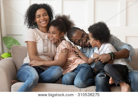 Happy African American Family Of Four Laughing Bonding On Sofa
