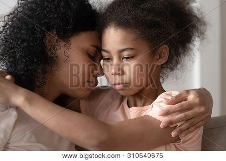 Thoughtful African American Kid Daughter Embracing Mom Bonding Cuddling