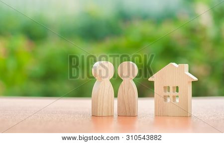 Two Wooden Figures Of People And A House On A Nature Background. Concept Of Affordable Housing, Mort