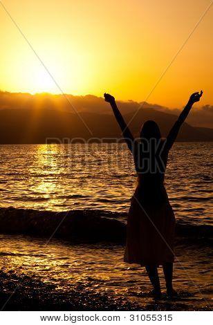Mladá štíhlá dívka si užívá svobody. Západ slunce a moře