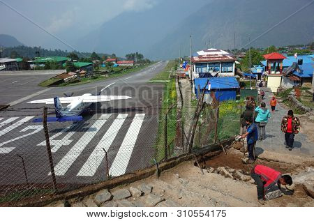 Lukla, Nepal - May 8, 2019: Nepali workers paving walkway next to fence of Tenzing–Hillary airport in Himalayas mountains