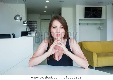 Close up portrait of a young confident serious woman with deep decollete, looking at the camera, holding hand near the face, looking seriously up against a office hall background. Copy space poster