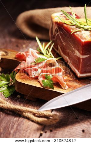 Italian Prosciutto Crudo Or Jamon With Rosemary. Raw Ham On Wooden Board