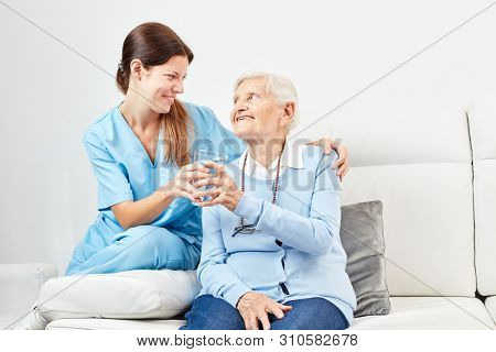 Smiling nursing help gives happy senior citizen a glass of water to drink