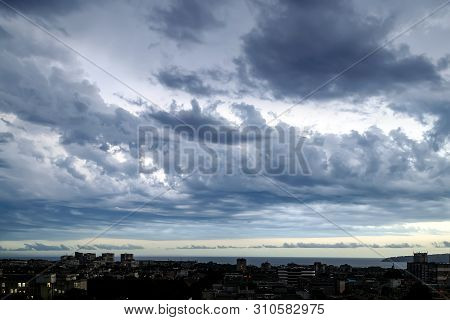 Dark stormy sky over a seaside city at summer evening. Dramatic skyscape with large gray clouds. Different cloud types and atmospheric phenomena. poster