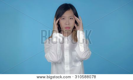 Young Asian Happy Woman Posing Has Headache Or Migraine On Blue Background In Studio. Attractive Mil