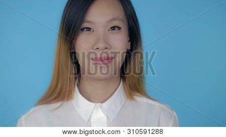 Close Up Portrait Young Asian Woman On Blue Background In Studio. Attractive Millennial Girl Looking