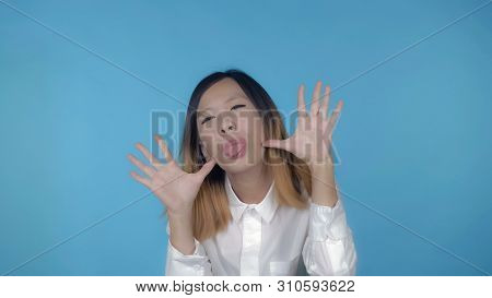 Young Asian Woman Posing Have Fun Making Faces On Blue Background In Studio. Attractive Millennial G