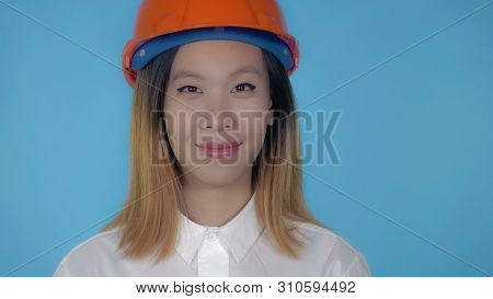 Close Up Portrait Young Asian Architect Orange Hard Hat On Blue Background In Studio. Attractive Mil