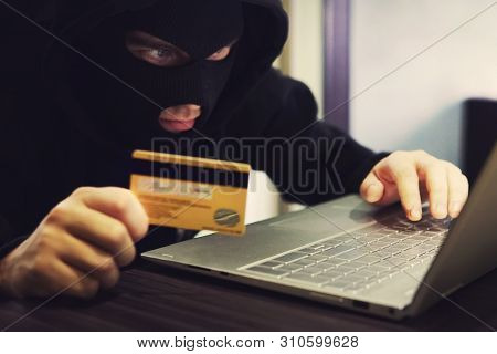 Man In Robber Mask And Hood Misappropriates Personal Bank Data. Cyber Fraudster Attacks Online Banki