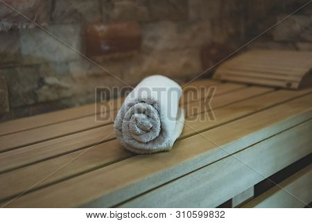 A Close Up Of A Rolled Bath Towel Lying On The Wooden Bathbed In Steam Room Of A Sauna. A Shot Of An