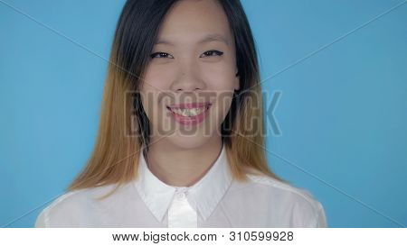 Close Up Portrait Young Asian Woman Laughing On Blue Background In Studio. Attractive Millennial Gir