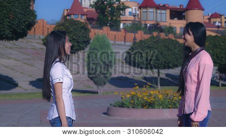Two Young Asian Women Meeting On The Street Greeting With Regards. Woman With Long Black Hair Wearin