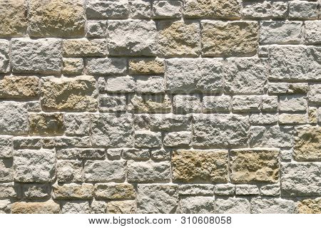 Background pattern created by the sun shining and creating shadows from the uneven textures and rough surfaces of stone bricks making up a fence or building exterior. poster