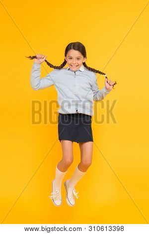 She is hyper. Happy energetic kid jumping on yellow background. Little girl with long hair braids feeling energetic. Small schoolchild getting energetic start to school year. Active and energetic. poster