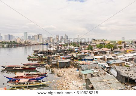 Manila Slums On The Background Of A Big City. Houses And Boats Of The Poor Inhabitants Of Manila. Dw
