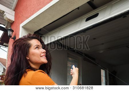 Garage Door Pvc. Girl Or Young Woman Holds Remote Controller For Closing And Opening Garage Door