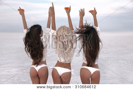 Girlfriend. Happy Three Female Friends In Sexy Bikini Having Fun On White Beach At Sunset. Group Of