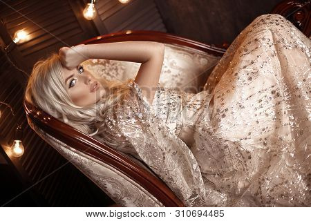 Elegant Blond Woman In Beige Dress Posing On Luxury Sofa In Royal Interior. Fashion Beautiful Sensua
