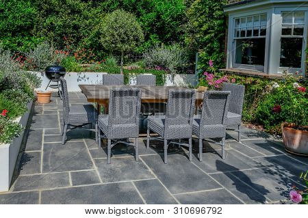 Wooden Table And Grey Wicker Chairs On A Modern Patio With A Round Bar-b-que In The Background.  Bea
