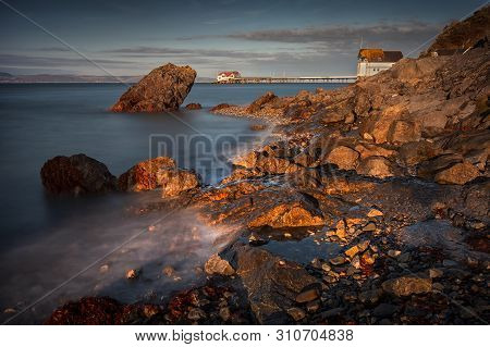 Evening Sunlight And A Long Exposure Of Knab Rock And Mumbles Pier In Swansea Bay, South Wales, Uk