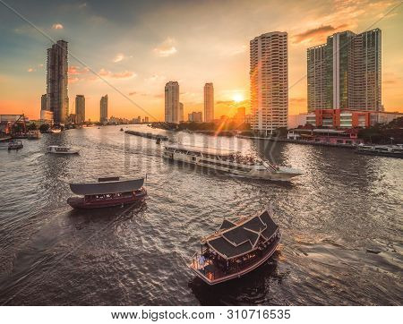 Busy Chao Phraya River With Passenger Boats And Skyscrapers At Sunset As Seen From Taksin Bridge In