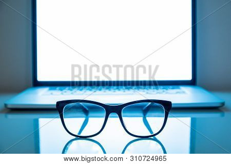 Computer Eyeglasses In Front Of A Laptop, Low-key Image. Blue Light Blockers And Laptop In Dark Back