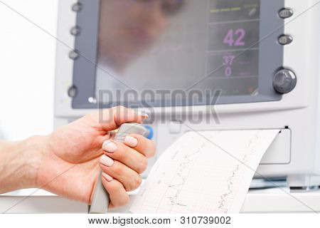 Close-up shot of pregnant woman's hand holding controller of the Cardiotocograph machine aka Electronic Fetal Monitor (EFM) recording the fetal heartbeat and the uterine contractions during pregnancy. poster