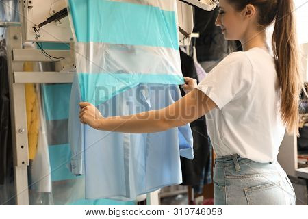 Female Worker Putting Garment Cover On Shirt In Dry-cleaning