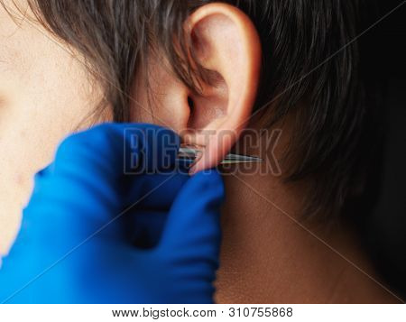 piercing and stretching the ears with medical  blue gloves. increase the diameter of the ear tunnels close-up poster