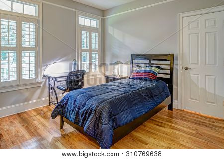Simple guest bedroom with single bed and windows.