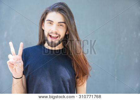 Happy Guy With Beautiful Long Hair Showing Peace Gesture. Cheerful Handsome Young Man Making V Sign