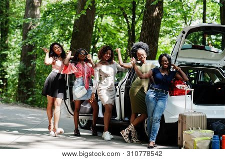Group Of Five Happy African American Traveler Girls Posed Against Car Open Trunk.