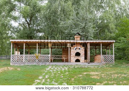 Summer Cafe In The Village. A Rural Bower For A Picnic In The Forest And A Brick Stove For Cooking O