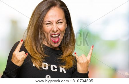 Beautiful middle age woman wearing rock and roll sweater shouting with crazy expression doing rock symbol with hands up. Music star. Heavy concept.